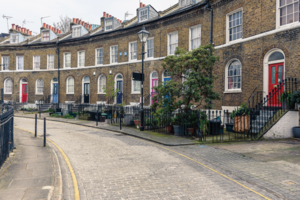 Curved north London housing terrace with colourful doors and cobbled street.