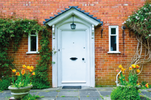 White front door with flower pots either side.