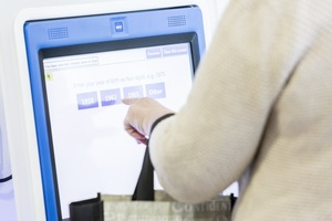 Patient using touch screen check-in at medical centre