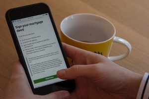 Two hands hold a smartphone with the screen showing the 'Sign your mortgage deed' website page.