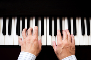 Man's hands playing the piano