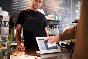 Person paying at a cafe using a tablet device.