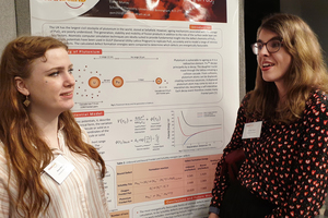 Two female research students study a project poster