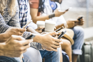 A row of people on their phones sitting next to each other