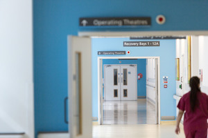 A nurse walking down a hospital corridor with a sign to the operating theatre.