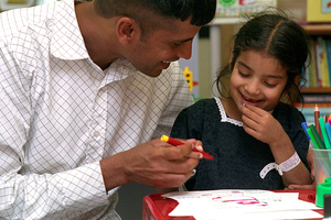 Adult carer talking to child in school