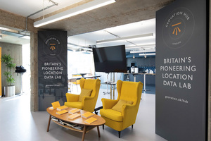 Photo of the Geovation Hub, showing comfortable armchairs, a desk with pamphlets and banners