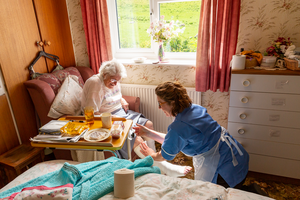 Nurse helping lady in her home