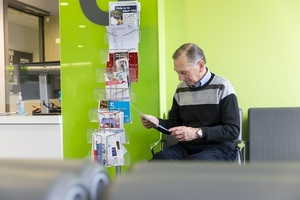 An older man sitting in a GP waiting area, reading a leaflet