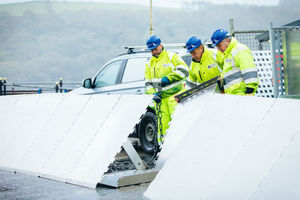Men in high visibility gear putting up L-shaped barriers made of metal
