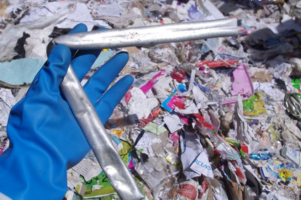 A hand in a blue glove holding a bent pipe with waste in the background