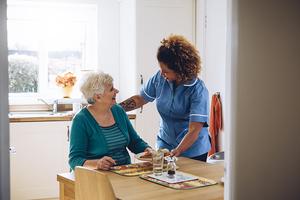 Nurse visiting elderly woman in her home.