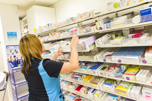 Pharmacist reaching for medicines in a hospital pharmacy