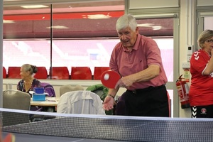 An elderly man playing table tennis