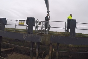 Two EA employees using a camera to inspect flood defences