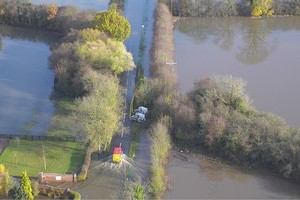 Aerial view of a flooded road and fields with two water pumps beside the road and an emergency vehicle moving along the road