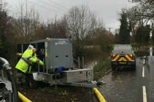 An Environment Agency officer operating a water pump next to a road with an EA vehicle parked nearby