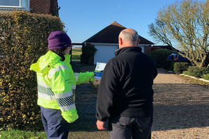 An Environment Agency officer helps a local resident sign up for flood warnings