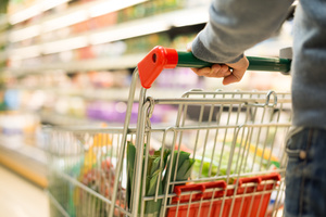 Man pushing supermarket trolley filled with groceries.