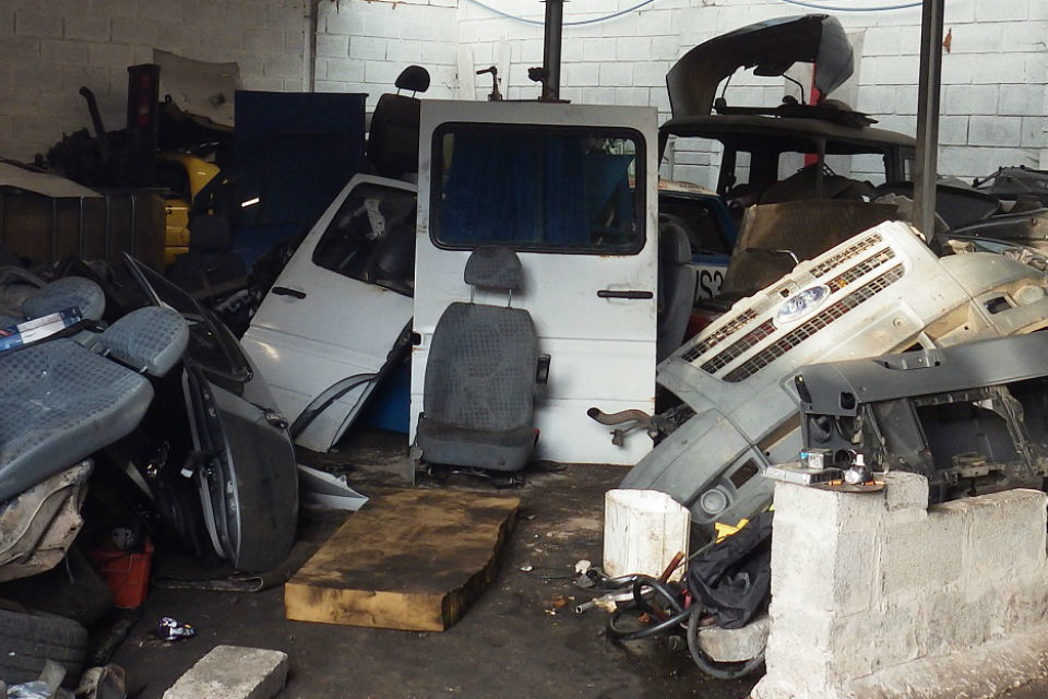 A van door, chairs and other car parts being stored inside a garage
