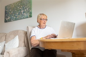 Older lady using laptop in her home