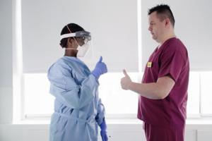 Two professionals in a clinical setting wearing PPE.