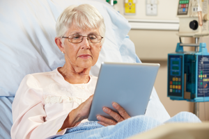 An older woman sitting in a hospital bed using a digital tablet