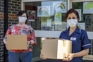 Social care workers wearing face masks and carrying boxes