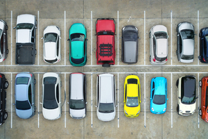 Cars parked uniformly in a parking lot.