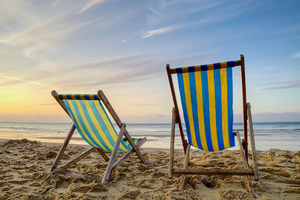 Two deck chairs on an empty beach