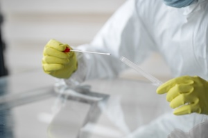 Lab worker holding swab test sample and test tube