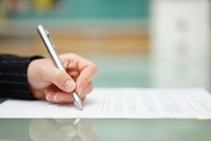 Stock image of a person writing on a piece of paper.