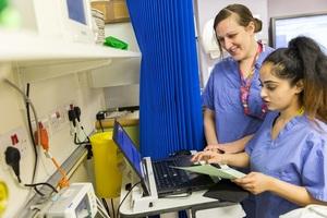 Two nurses looking a screen