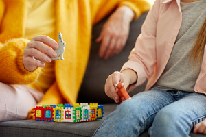 Image showing a child with toys and an adult sitting on a sofa