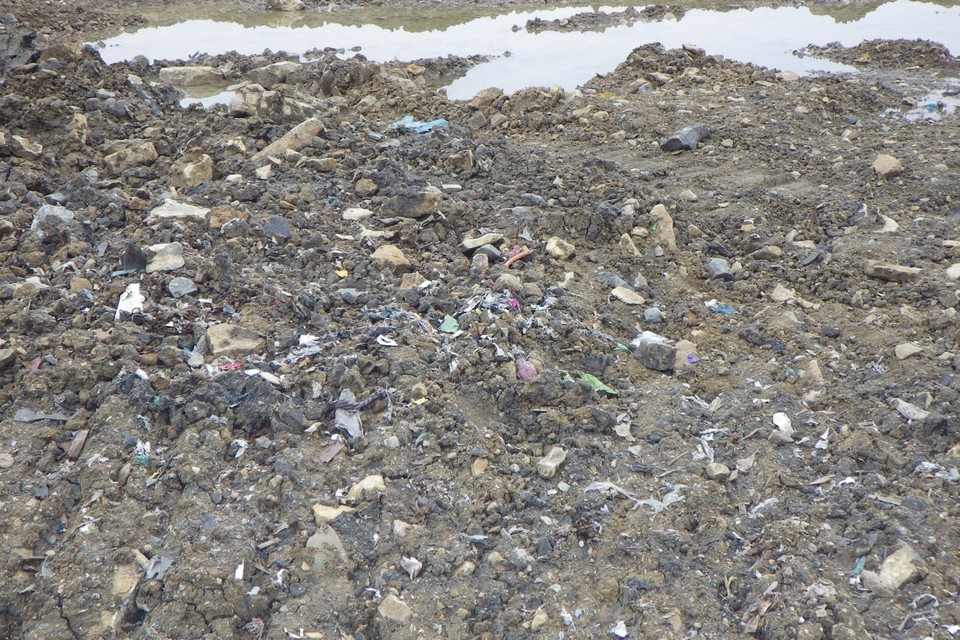 Close up picture of the ground which is littered with plastic shreds and other material