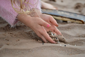Girls hands holding sand on the beach which has plastic nurdles in it