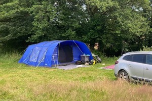 A large blue tent pitched below some trees in a grassy field.