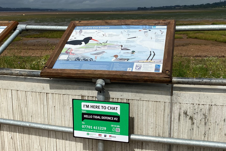 Sign saying I'm here to chat with number you can text for information about the Exmouth tidal defence scheme